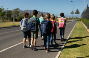 Front view of a diverse group of schoolchildren walking along a road to elementary school together in the sun, smiling to camera